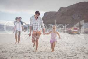 Happy family running on sand
