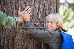 Smiling son with father father touching tree trunk in forest