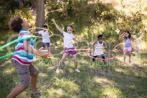 Cheerful friends playing with hula hoops at campsite