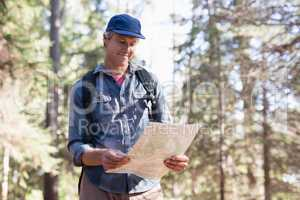 Happy hiker reading map in forest