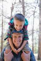 Happy boy sitting on shoulders of father in forest
