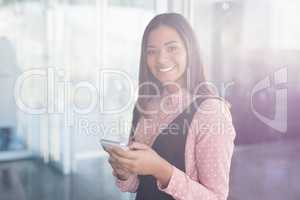 Portrait of smiling businesswoman using mobile