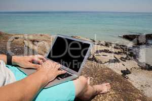 Man sitting on the rocks and using laptop at the sea coast