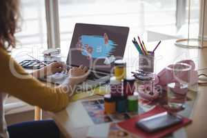 Cropped image of businesswoman typing on laptop at office
