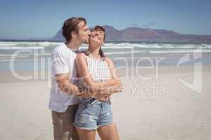 Young man kissing woman at beach