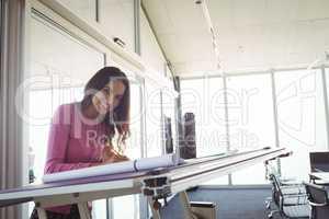 female designer making diagram on paper in creative office