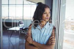 Thoughtful young businesswoman looking through window