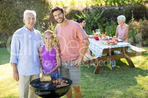 Girl, father and grandfather preparing barbecue in the park