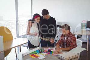 Business colleagues discussing over color swatch at creative office