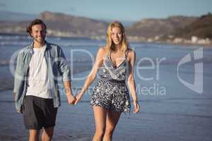 Portrait of happy couple holding hands on shore