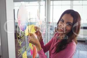 Smiling female designer holding adhesive note on glass in creative office