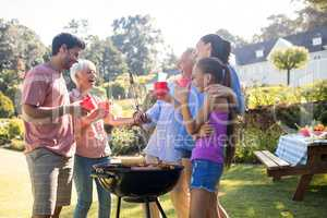 Family laughing and talking while preparing barbecue in the park