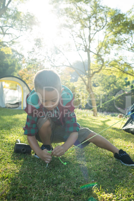 Boy setting up the tent at campsite