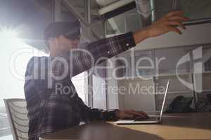 Businessman wearing virtual reality headset while using laptop in office