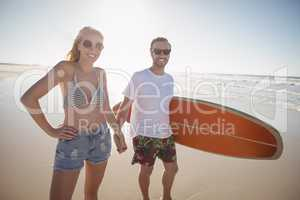 Happy couple holding hands at beach during sunny