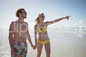 Woman gesturing while holding man hands at beach