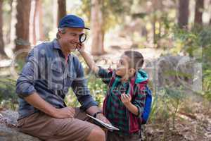 Boy showing magnifying glass to father while hiking in forest