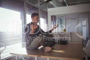 Businessman meditating on table at office