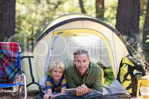 Smiling father and son with digital tablet resting in tent at campsite