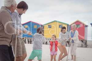 Family playing tug of war at beach