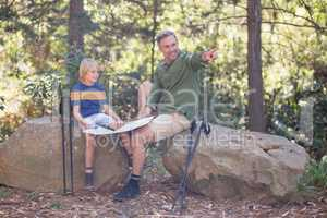 Father showing direction to son in forest