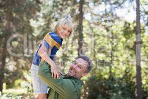 Portrait of playful father lifting up son