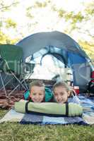 Smiling siblings lying outside the tent