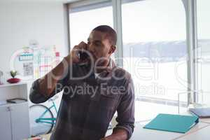 Serious businessman talking on phone in office