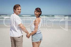 Portrait of young couple holding hands at beach
