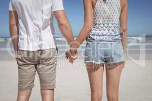 Mid section of young couple holding hands at beach