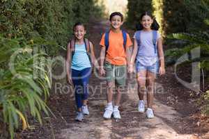 Portrait of smiling friends carrying backpack at natural parkland