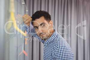 Thoughtful executive leaning on whiteboard
