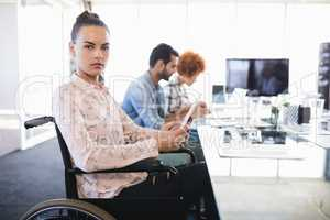 Portrait of businesswoman using digital tablet while sitting on wheelchair