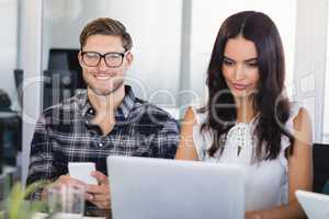 Smiling businessman sitting with female colleague at office