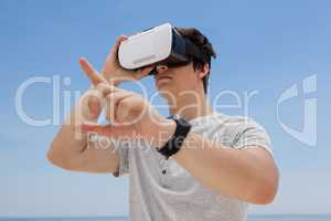 Man using vr headset against the blue sky