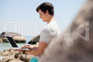 Man leaning on the rocks and using laptop at the sea coast