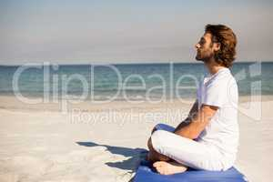 Man performing yoga at beach