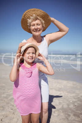 Portrait of girl with grandmother wearing sun hat at beach