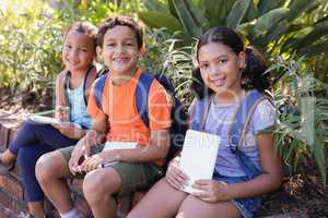 Friends holding books while sitting on retaining wall at natural parkland