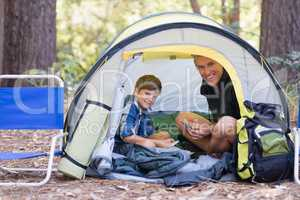 Father and son sitting inside tent while hiking in forest