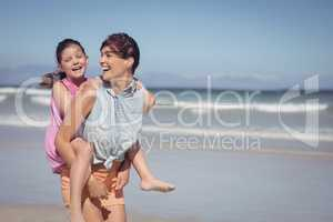 Cheerful mother piggybacking daughter at beach