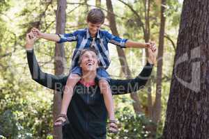 Cheerful father carrying son on shoulders in forest