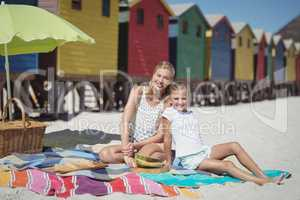 Portrait of smiling woman with her daughter sitting on blanket at beach