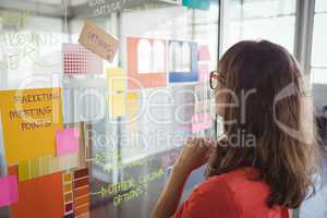 Businesswoman planning with adhesive notes on glass in office