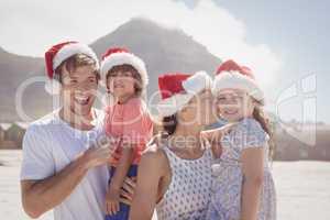Cheerful family wearing Santa hat at beach