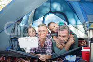 Smiling family taking selfie in the tent