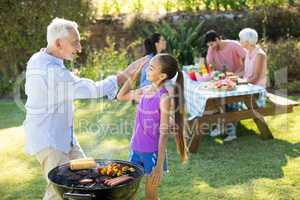 Grandfather and granddaughter giving a high five while preparing barbecue