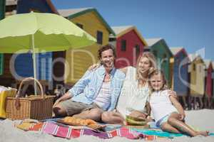 Portrait of fappy family sitting on blanket at beach