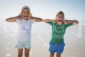 Siblings making teasing faces at beach