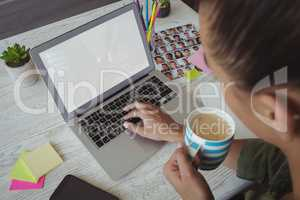 Female photo editor holding coffee cup while using laptop in office